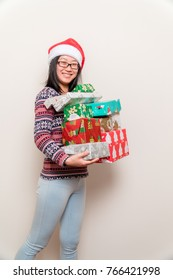 Chirstmas gift topic: a happy young woman holding a stack of Christmas presents.