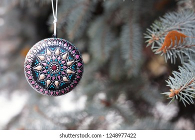 Chirstmas tree decor, ball with painted mandala star on in. New year holiday background