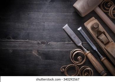 Chisels shaving plane lump hammer planning chips on wooden board.
