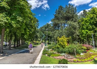 Chisinau, Moldavia - July 4th 2018 - Locals walking near by an amazing public garden through the trees in a blue sky in Chisinau, the capital of Moldavia