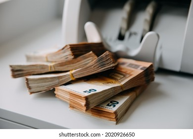 Chisinau, Moldova - August 1, 2021: Closeup of packs of fifty euro banknotes next to a counting machine.