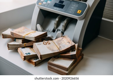 Chisinau, Moldova - August 1, 2021: Fifty euro banknotes next to a counting machine.