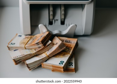 Chisinau, Moldova - August 1, 2021: Packs of fifty euro banknotes next to a counting machine.