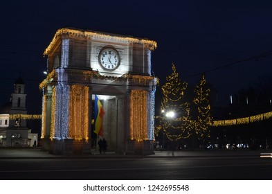 Chisinau, Moldova - December 31, 2017: Center of Chisinau city with decorated Arch of Triumph and evergreen trees during winter holidays season. Night photo.