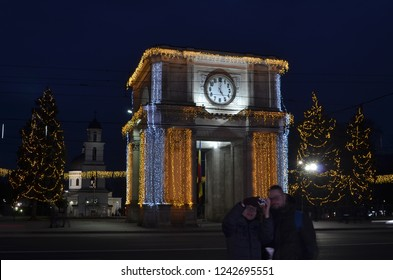 Chisinau, Moldova - December 31, 2017: Young couple is making self portrait photo in center of Chisinau city with decorated Arch of Triumph in background during winter holidays season. Night photo.