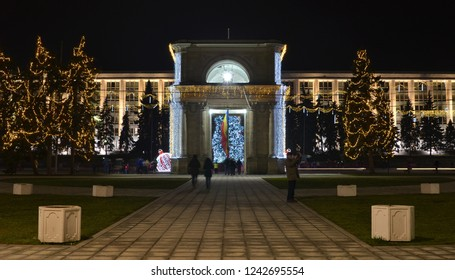 Chisinau, Moldova - December 31, 2017: Center of Chisinau city with decorated Arch of Triumph, evergreen trees and government building in background during winter holidays season. Night photo.