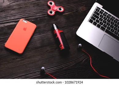 Chisinau, Moldova - February 20, 2018: iphone in red case, mod vape, fidget spinner, headphones and apple macbook pro on wooden desk