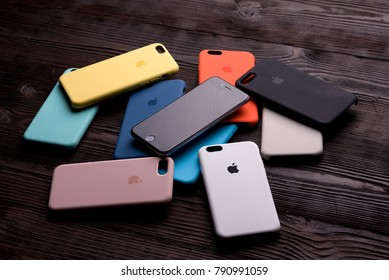 Chisinau, Moldova - January 11, 2018: nine different-colored cases for smartphone and new iphone on brown wooden table