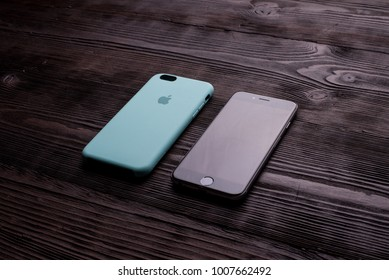 Chisinau, Moldova - January 23, 2018: new black iPhone with turquoise case on brown wooden table