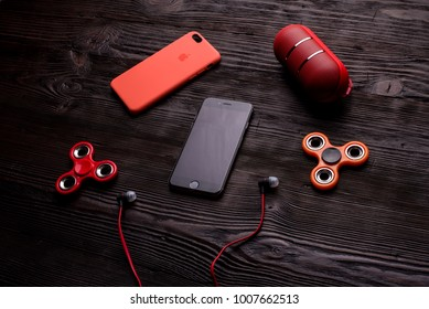 Chisinau, Moldova - January 23, 2018: black iPhone with red case, headphones, two red fidget spinners and red bluetooth spealer on brown wooden table