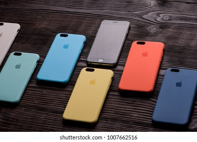 Chisinau, Moldova - January 23, 2018: black iPhone with six different-colored cases on wooden table