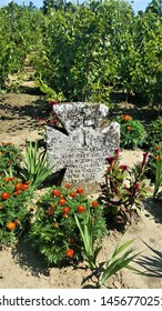 Chisinau, Moldova - July 22, 2018: Village museum. Very old grave cross surrounded by flowers and grape vines. Year 1821 engraved, and text using cyrillic alphabet.