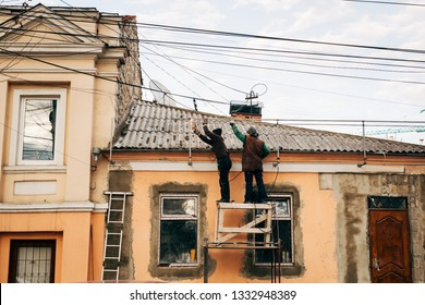 Chisinau, Moldova - March 2019: Two construction workers working dangerously without safety measures. Careless welders on an improvised scaffolding.