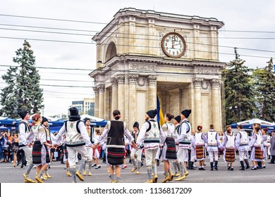 CHISINAU, MOLDOVA - OCTOBER 14, 2017: People dancing national Hora dance near Arch of Triumph at city day. Clouds on background
