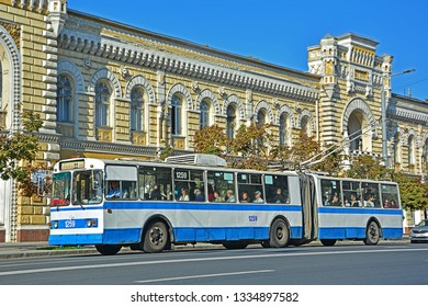 CHISINAU, MOLDOVA - SEPTEMBER 1, 2017 - Old articulated ZiU-10 trolleybus, operated by RTEC Chisinau, on Stefan cel Mare street, with the historic City Hall building in the background