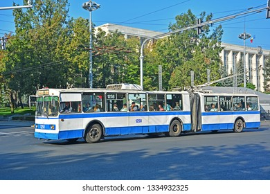 CHISINAU, MOLDOVA - SEPTEMBER 1, 2017 - Old articulated ZiU-10 trolleybus, operated by RTEC Chisinau, on Stefan cel Mare street, with the government house building in the background