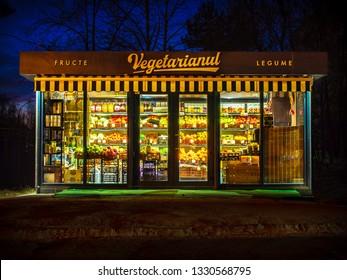 CHISINAU, MOLDOVA-MARCH 5, 2019: Vegetarian fruit shop at night (inscription in romanian: fruits, vegetables, vegetarian)