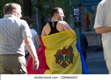 Chisinau, Rep. of Moldova - August 27, 2016: Man covered in Moldavian flag walking on the street during Independence Day celebrations in Chisinau, Moldova