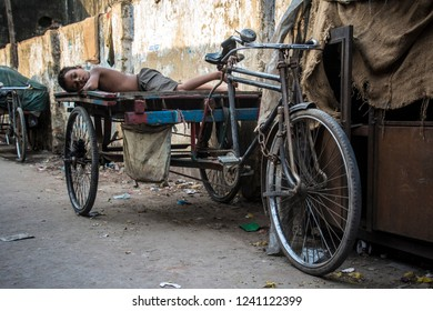 Chittagong, Bangladesh - Apr 27 2018: Boy taking a nap on the rikshaw platform in the Chittagong street