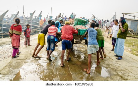 Chittagong, Bangladesh, December 23, 2017: Fishermen are pushing cart loaded with fresh catch of shrimp at a port in Chittagong, Bangladesh