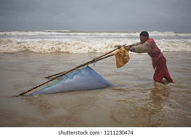 Chittagong, Bangladesh, July 2009 - A shrimp fisherman working in the water at Cox's Bazar beach, the world's largest.