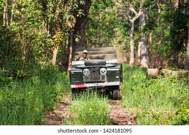 CHITWAN NATIONAL PARK, NEPAL - CIRCA MAY 2019: A vintage Land Rover Series II is being driven in Chitwan National Park jungle. The car has been modified for safari purpose.