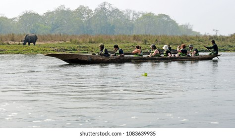 CHITWAN, NEPAL-February 19, 2017: A group of tourists in a canoe watching a rhino at close distance at Chitwan National park in Nepal