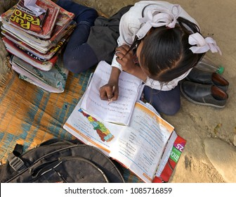 CHITWAN, NEPAL-FEBRUARY 21, 2017:Young female student doing her school homework sitting on the ground. Chitwan District in Nepal has declared 100% literacy.