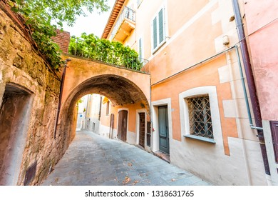 Chiusi, Italy street in small historic medieval town village in Umbria during sunny day with nobody orange yellow pink vibrant colorful walls and arch