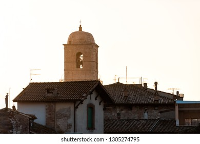 Chiusi mist fog sunrise of Cathedral Church bell tower in Umbria, Italy near tuscany with warm sepia orange golden yellow brown vintage color cityscape