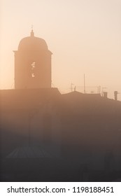 Chiusi mist fog sunrise of famous Cathedral Church bell tower in Umbria, Italy near tuscany, with warm sepia soft orange golden yellow pink brown vintage color, vertical view