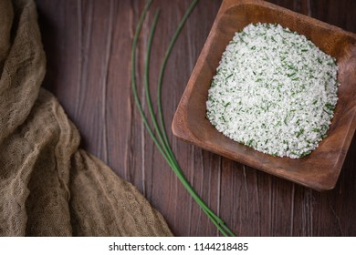 Chives Herb Salt in Small Wooden Bowl; Fresh sprig of herb on Wooden Tabletop beside the bowl