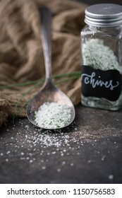 Chives Herb Salt in Tarnished Spoon on Black Background with Fresh Sprigs of Chives