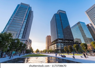 CHIYODA, TOKYO / JAPAN - AUGUST 25 2018 : The landscape of Tokyo Marunouchi where the sunset glows. The sun will set between the office buildings. Many tourists were gathering in the plaza.