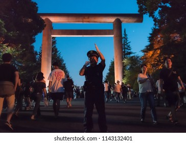 Chiyoda, Tokyo / Japan - July 15th 2018: A policeman ensure security at the Mitama Matsuri festival in summer at the shinto shrine Yasukuni Jinja in Tokyo.