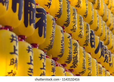 Chiyoda, Tokyo / Japan - July 15th 2018: The famous yellow lanterns showing the sponsors of the Mitama Matsuri festival in summer at the shinto shrine Yasukuni Jinja in Tokyo.