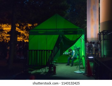 Chiyoda, Tokyo / Japan - July 15th 2018: Green tent and an organisation staff at the Mitama Matsuri festival in summer at the shinto shrine Yasukuni Jinja in Tokyo.