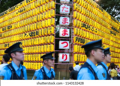 Chiyoda, Tokyo / Japan - July 15th 2018: Policemen take car that everything is safe during the Mitama Matsuri festival in summer at the shinto shrine Yasukuni Jinja in Tokyo.