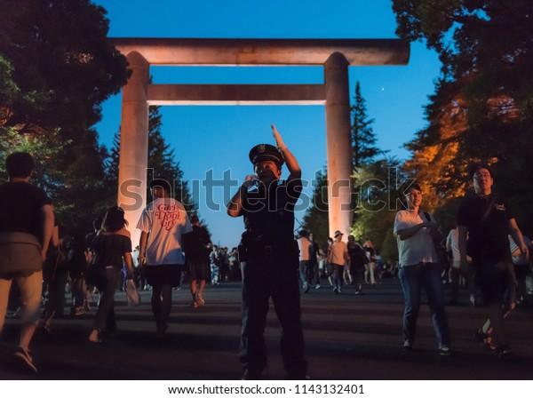 Chiyoda, Tokyo / Japan - July 15th 2018: A policeman ensure security at the Mitama Matsuri festival in summer at the shinto shrine Yasukuni Jinja in Tokyo.