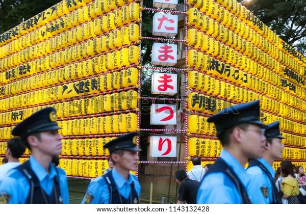 Chiyoda, Tokyo / Japan - July 15th 2018: Policemen take car that everything is safe during the Mitama Matsuri festival in summer at the shinto shrine Yasukuni Jinja in Tokyo.