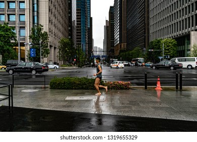 Chiyoda, Tokyo, Japan - June 13 2016 - A man runs barefoot in the rain in front of The Imperial palace. Japan is a country with a passion for running and jogging.