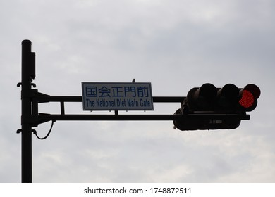 Chiyoda, Tokyo / Japan - June 17 2015: The National Diet Main Gate (Kokkai) sign and red traffic light against cloudy sky in Chiyoda, Tokyo, Japan.