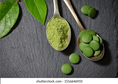 Chlorella And Barley Powder On Spoons on ardesia plate