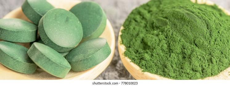chlorella, spirulina green algae in powder and tablets form- closeup, macro shot