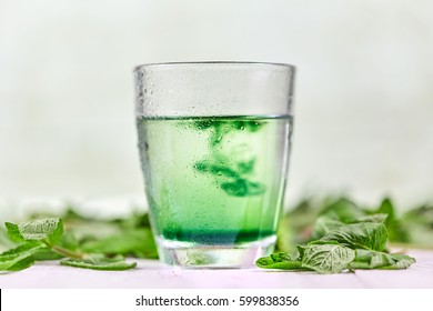 Chlorophyll in glass of water with fresh green mint on white table