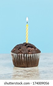 Choc chip muffin with a lit candle depicting a celebration