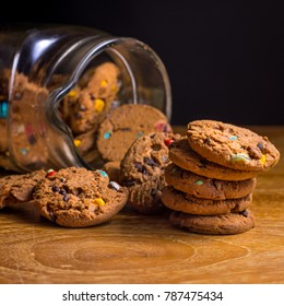 Choc chip smartie cookies falling out of jar on wooden table top.