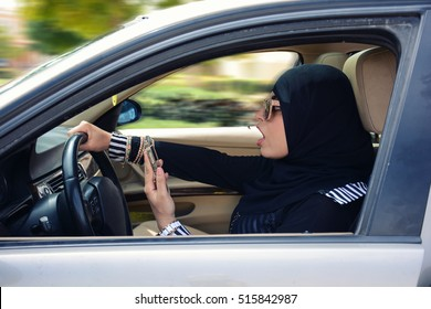 chocked arabic woman using mobile while driving, wearing hijab and abaya, driving danger