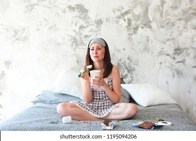 Chocoholic. Cheerful sad young craing woman eating sweets in her bedroom. Emotional woman with eating icecream and crying after divorce. Stress concept