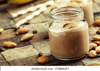 Chocolate almond smoothie in glass jars, old wooden background, selective focus